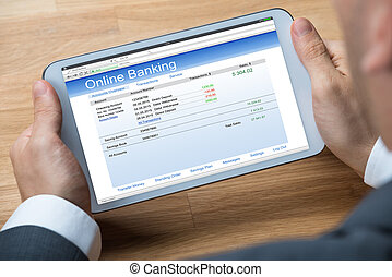 Businessman Doing Online Banking On Digital Tablet - Cropped...