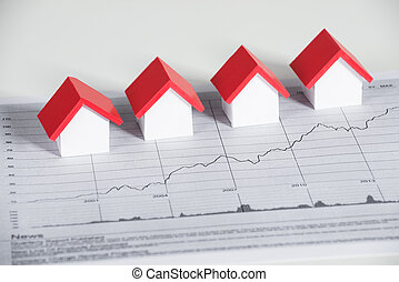 House Models On Financial Chart At Desk - High angle view of...