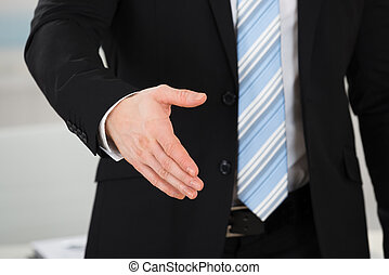 Businessman Offering Handshake In Office
