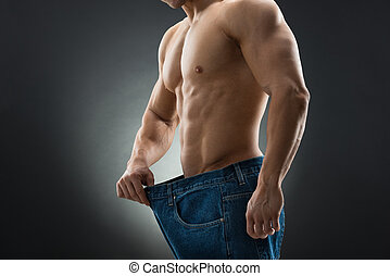 Midsection Of Muscular Man In Old Jeans Showing Weight Loss...