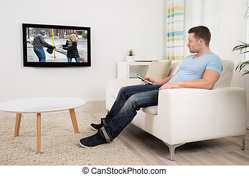 Man With Remote Control Watching Movie In Living Room