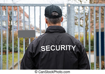 Security Guard Standing In Front Of Gate