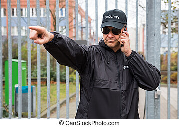 Security Guard Gesturing While Using Walkie-Talkie - Serious...