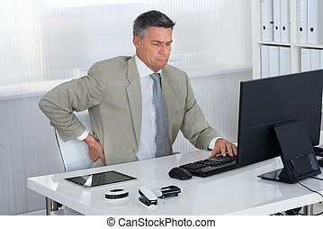 Mature Businessman Suffering From Back Pain At Desk - Mature...