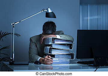 Businessman Leaning Head On Binders While Working Late -...