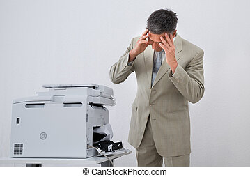 Businessman Looking At Paper Stuck In Printer - Irritated...