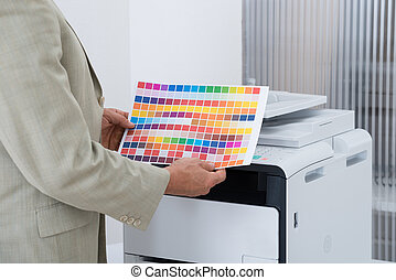Businessman Holding Multi Colored Paper By Printer -...