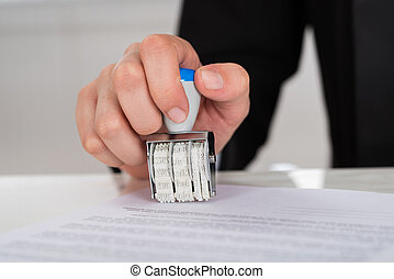 Businesswoman Stamping Contract Paper At Desk - Cropped...