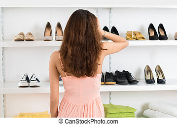 Confused Woman Looking At Shoes Displayed On Shelves - Rear...