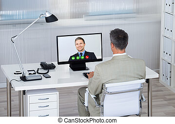 Businessman Videoconferencing With Partner On Computer At...