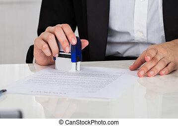 Businesswoman Stamping Contract Document At Desk - Cropped...