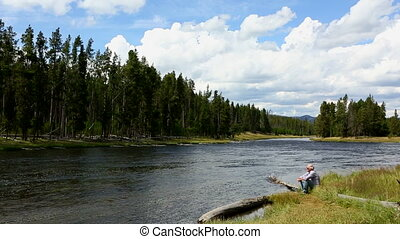 Firehole River Yellowstone National - Senior adult sits on a...