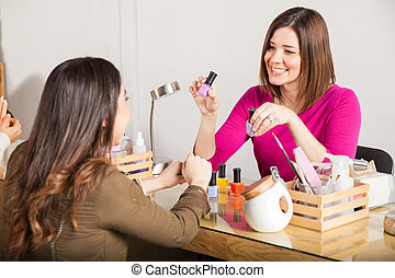Manicurist recommending her favorite color - Beautiful young...