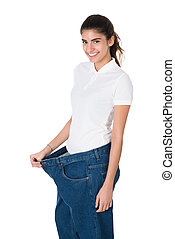 Smiling Woman Showing Her Old Jeans After Successful Diet -...