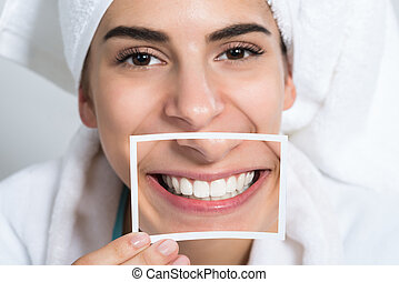 Woman Holding Photo Of Toothy Smile - Beautiful young woman...