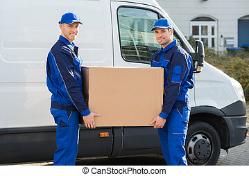 Delivery Men Carrying Cardboard Box Against Truck - Portrait...