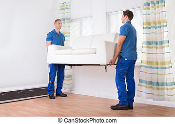 Movers Carrying Sofa At Home - Full length of young movers...