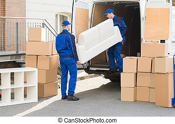 Movers Unloading Sofa From Truck - Young male movers...