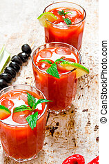 Cocktails made of tomatoes, vodka, ice, lime, pepper , salt and snack with celery and black olives on rustic background .