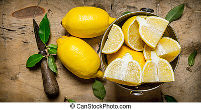Fresh lemons in a bucket with leaves and knife. On a wooden...