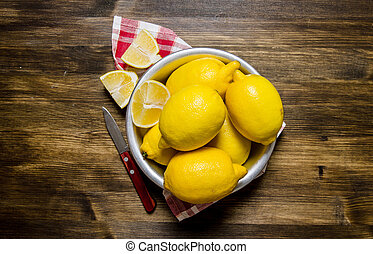 The lemons in the cup with a knife on the fabric. On a...