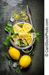Fresh lemons in a saucepan with leaves and zest. On the...