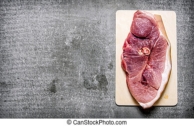 A piece of fresh raw meat on wooden Board. On the stone...