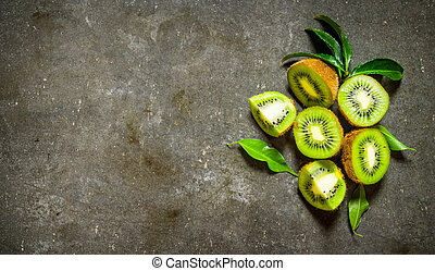 Kiwi with leaves . On stone table .