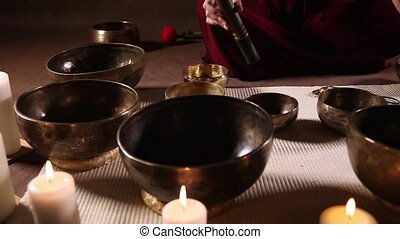 Tibetan singing bowls dolly shot - Woman playing small...