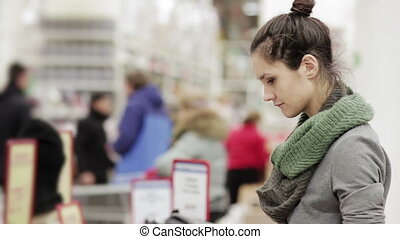 Young woman chooses winter hat in the supermarket - young...
