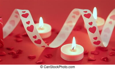 Red roses and chocolate candies with candles for Valentines...
