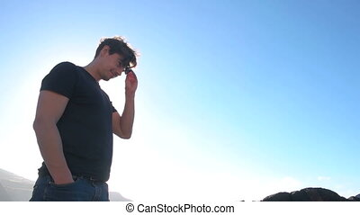 Low angled shot of man putting on sunglasses
