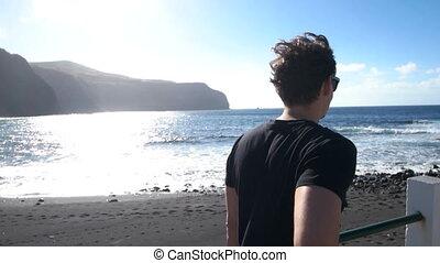 Eye leveled shot of man walking next to the beach