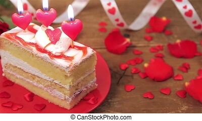 Decorated cake with candles and roses on wooden table for...