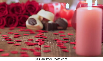 Red roses and chocolate candies with candles on wood for...