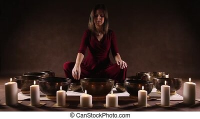 Woman playing Tibetan singing bowls - Woman sitting and...