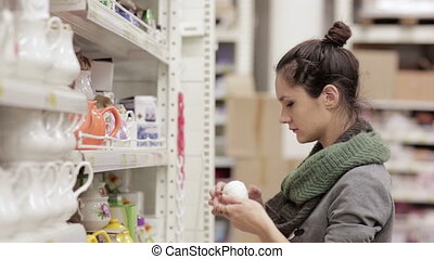 Young woman chooses dishes in the supermarket - young woman...