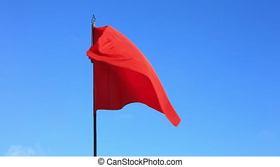 Red flag flapping in blue sky - Scarlet red flag at blue sky...