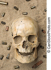 skull lying in the sand, scattered rifle and pistol...