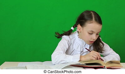 Little girl diligently doing their homework Green screen...