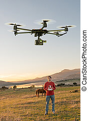 Man guiding a drone - Man in a rural environment guiding a...