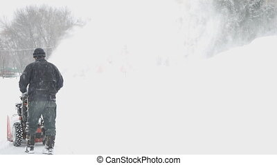 A man removes snow using snowblower - man runs a snowplow...