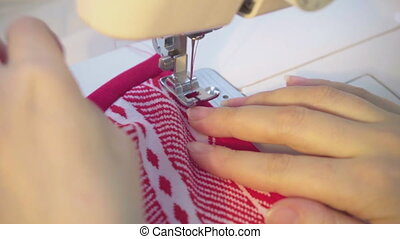 dressmaker works on the sewing machine - Women sewing with...