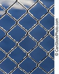 Chain link fence with snow on blue sky