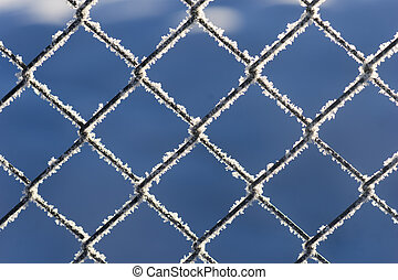 Chain link fence with snow crystals on blue sky
