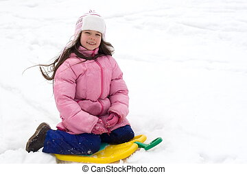 Cute Girl Sitting on a Snow Sled