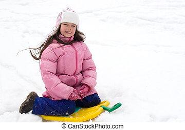 Cute Girl Sitting on a Snow Sled