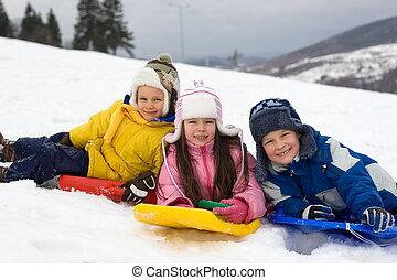 Kids Sliding in Fresh Snow - Three happy children enjoying...