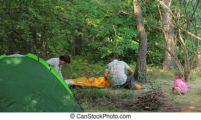 Family Setting Tents In Green Forest