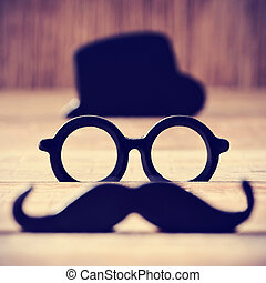 mustache, eyeglasses and hat forming the face of a man - a...